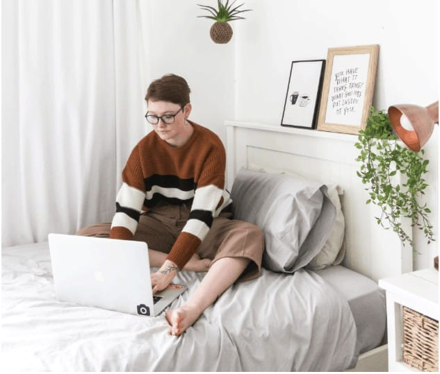 mom sitting on her bed looking at 7 of the Best Online Tutoring Jobs - Make up to $60 per hour!