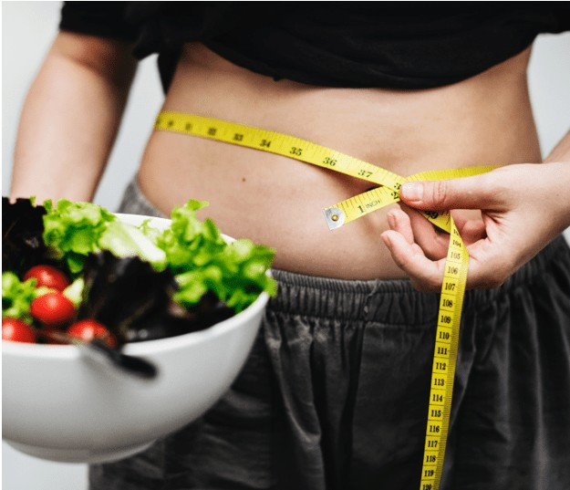 woman measuring her waist holding a salad - Weight Loss Challenge for Money