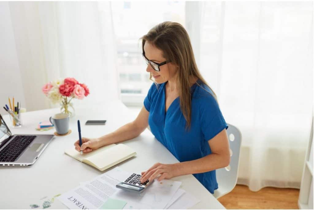woman sitting at a desk working on virtual bookkeeping