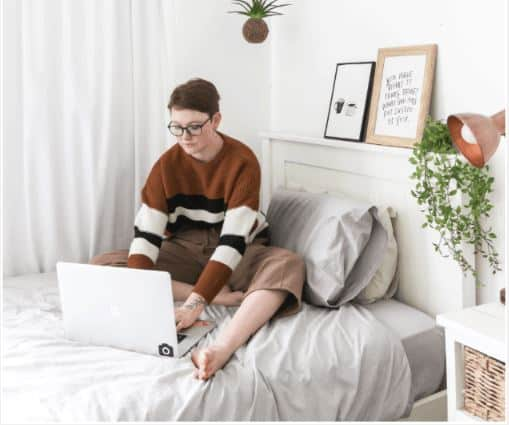 woman sitting on her bed on her laptop working as an online tutor