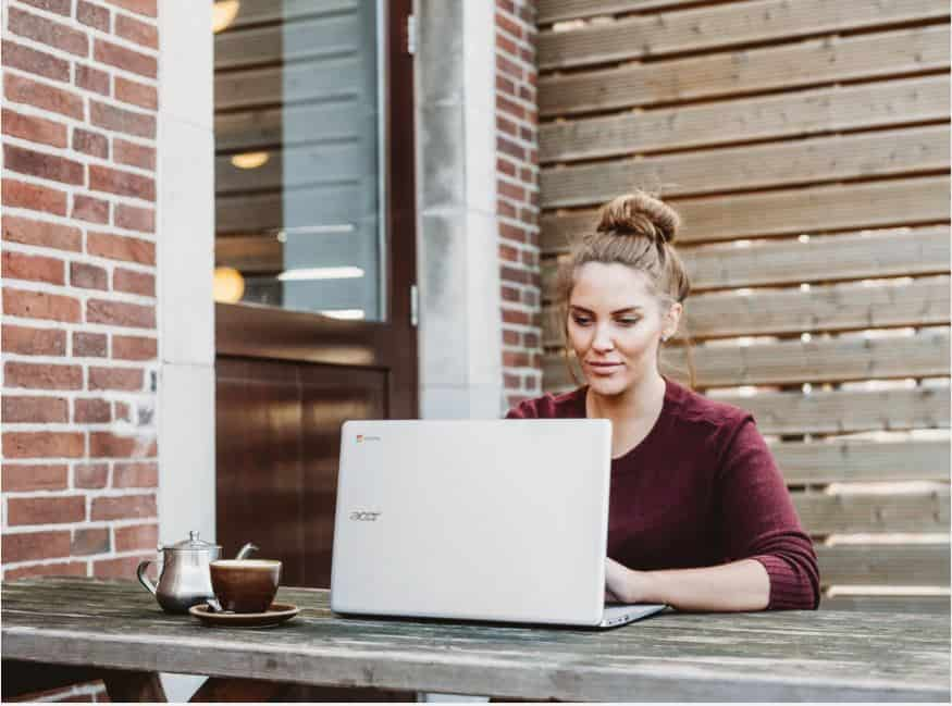 woman sitting outside on her laptop working on freelance jobs