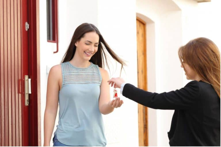 woman accepting keys after getting into real estate