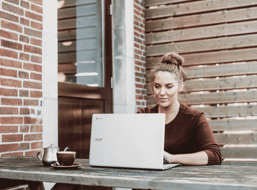 women outside on her laptop working on become a virtual assistant